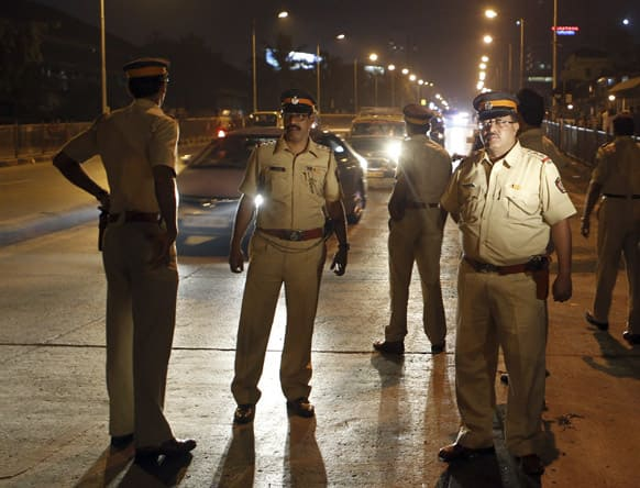 Police officers keep vigil on a road after security was enhanced in Mumbai, following twin explosions in southern Indian city of Hyderabad.
