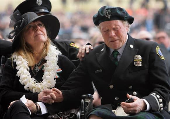 Dawn MacKay sits next to her husband Alan MacKay as he breaks down in tears while watching a video tribute of their son, San Bernardino County Sheriff Det. Jeremiah MacKay at the San Manuel Amphitheater in Glen Helen, Calif.