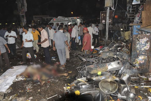 People gather on the scene after a bomb blast in Hyderabad.