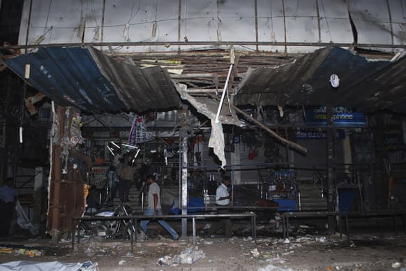 People walk past a damaged bus waiting shelter after a bomb blast in Hyderabad.
