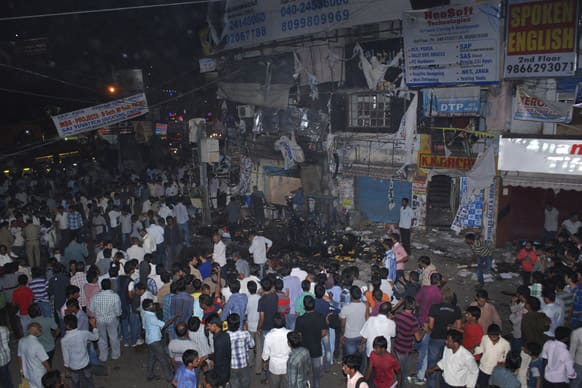 People gather on the scene after a bomb blast in Hyderabad. At least 11 people were killed and 50 injured Thursday in a pair of explosions in a crowded area of the southern Indian city of Hyderabad, officials said.