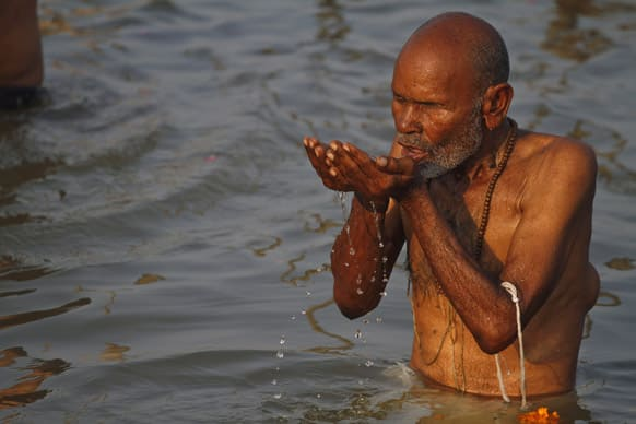 An elderly Hindu devotee drinks water from the Ganges River as he bathes near Sangam, the confluence of Hindu holy rivers of Ganges, Yamuna and the mythical Saraswati, at the Maha Kumbh festival in Allahabad.