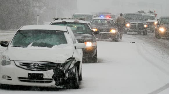 Wichita Police work an accident on west Kellogg during the snow-packed morning commute in Wichita, Kan.
