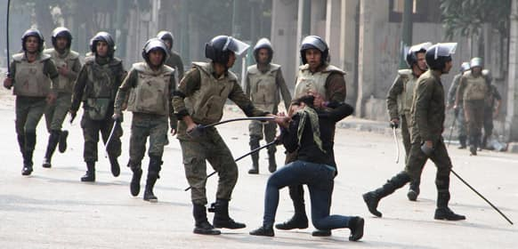 Egyptian army soldiers arrest a woman protester during clashes with military police near Cairo`s downtown Tahrir Square.
