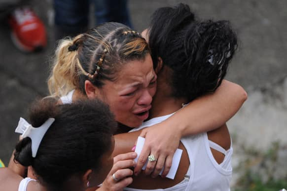 Women embrace during the funeral procession for Esteban Alvarez and Esleider Asprilla, both 11, at the Comuna 13 neighborhood in Medellin, Colombia.
