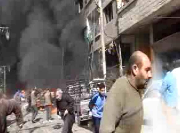 This image taken from video obtained from Ugarit News, which has been authenticated based on its contents and other AP reporting, shows smoke and fire after a fighter jet crashed into a suburb of Damascus, Syria.