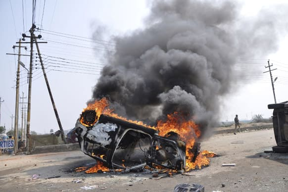 A policeman runs past a burning car set on fire by vandals on the first day of a two-day strike in Noida.