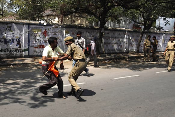 A policeman detains a worker who tried to march towards the state legislature complex on the first day of a two day strike in Hyderabad.