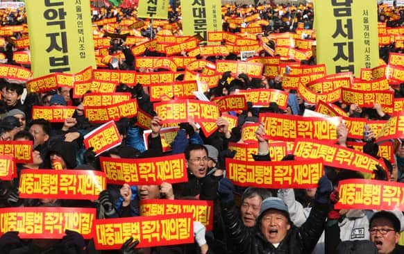 Taxi drivers shout slogans during a rally against government policy near the National Assembly in Seoul.