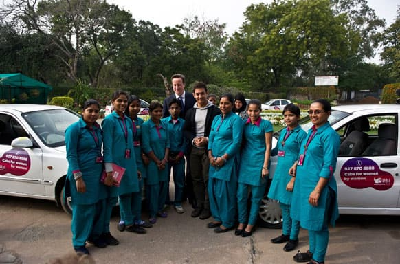 British Prime Minister David Cameron, center left, and Indian Bollywood actor Aamir Khan, center right, pose with Indian women cab drivers from Sakha cab services at the Janki Devi Memorial College in New Delhi.