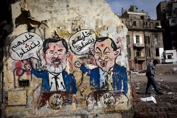 An Egyptian man walks by a mural depicting ousted president Hosni Mubarak, right, and Egyptian President Mohammed Morsi, left, with Arabic that reads