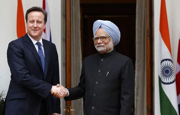 Manmohan Singh and British Prime Minister David Cameron shake hands before a meeting in New Delhi.