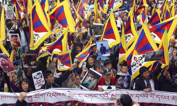 Exile Tibetans wave Tibetan flags and display photos of Tibetans who died in self-immolation as they demonstrate in Dharamsala.