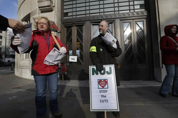 BBC journalists hand out leaflets as they mount picket lines after launching a 24-hour strike in a row over jobs, outside the BBC Broadcasting House, in central London.