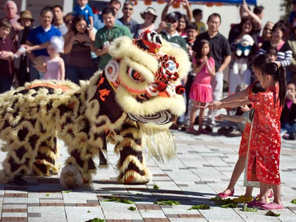 Three girls deliver red envelopes to the lion during the Lion Dance at a Lunar New Year celebration in Tustin, Calif.