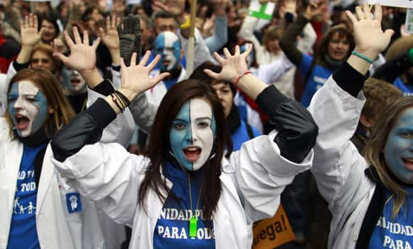 Protesters march as they shout slogans during a demonstration against regional government-imposed austerity plans to restructure and part-privatize the health care sector in Madrid, Spain.