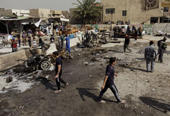 Iraqis inspect the scene of a car bomb attack in the Ameen neighborhood in eastern Baghdad, Iraq.