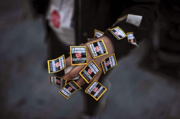 A hand of demonstrator displays stickers against evictions, in Pamplona, northern Spain.