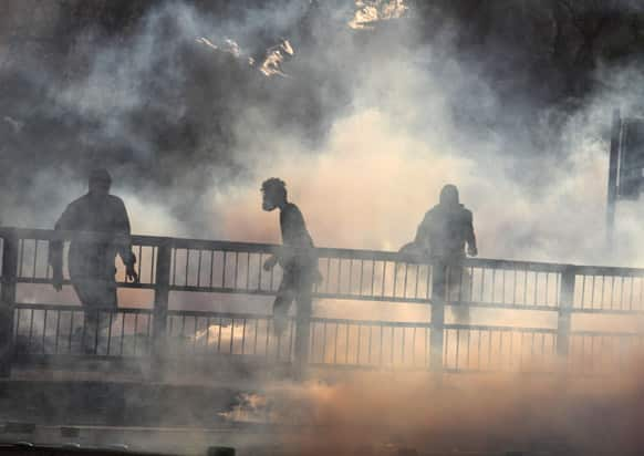 Bahraini anti-government protesters stand in clouds of tear gas fired by riot police during clashes in Daih, Bahrain.