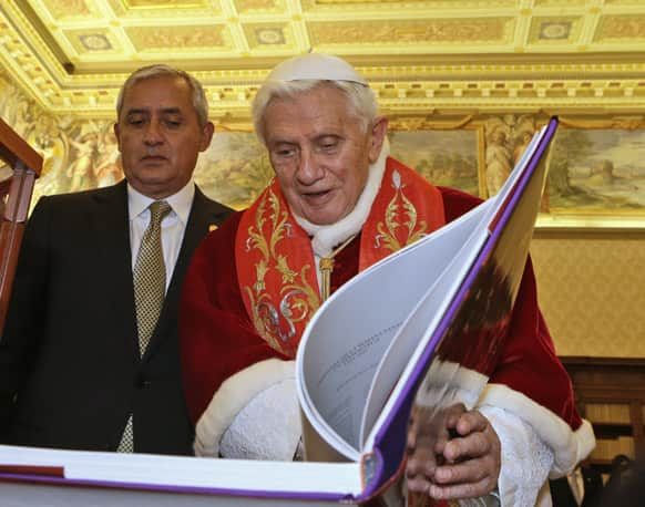 Pope Benedict XVI exchanges gifts with Guatemala`s President Otto Perez Molina, during a private audience at Vatican.