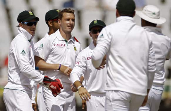 South Africa`s Dale Steyn, second left, reacts with team members after taking the wicket of Pakistan Mohammad Hafeez, unseen, during a five day test series in Cape Town, South Africa.