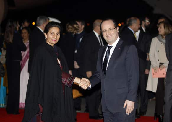 French President Francois Hollande shakes hands with India`s Junior Foreign Minister Preneet Kaur, upon arrival at the Palam Technical airport in New Delhi.