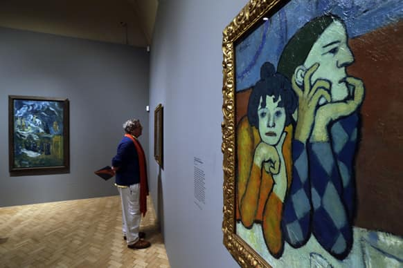 Members of the press walk through a gallery as an oil on canvas 1901 Pablo Picasso painting entitled `Harlequin and Companion` is seen, during a press view of an exhibition in central London.