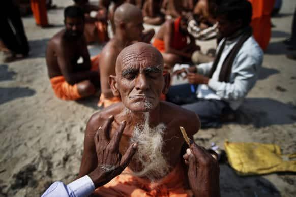 Hindu holy men get their beard and head shaved before being initiated as Naga sadhus or naked Hindu holy men at the Maha Kumbh festival in Allahabad.