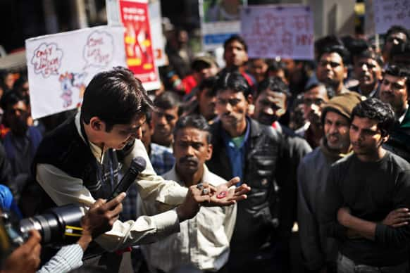 People watch as a volunteer of AIDS Healthcare Foundation (AHF) demonstrates the use of a condom at a red light area in New Delhi. AHF is observing Feb.13, the eve of Valentine's Day as International Condom Day.