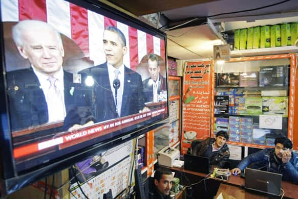 Afghan men watch a television news report on US President Barack Obama`s State of the Union address in Kabul. President Obama announced plans to withdraw more troops from Afghanistan and take steps to boost the fragile US economy.