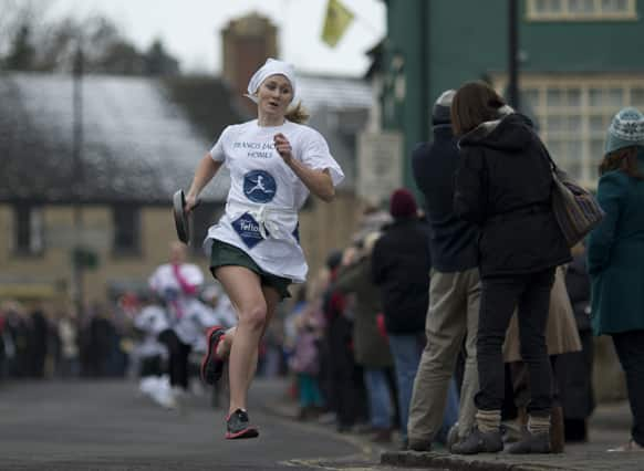 First place finisher 19-year-old Devon Byrne from Olney, leads the field en route to winning the annual Shrove Tuesday trans-Atlantic pancake race in a record time of 56 seconds, in the town of Olney, in Buckinghamshire, England.