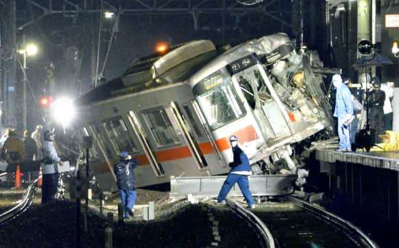 A derailed train is seen on a station platform after a collision at a railway crossing in Takasago, Hyogo prefecture. A commuter train collided with a truck at a railway crossing in southern Japan on Tuesday, injuring more than a dozen people.