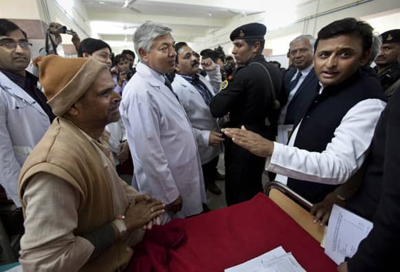 Uttar Pradesh Chief Minister Akhilesh Yadav, speaks with a survivor of a stampede at a railway station, during a visit to meet with injured pilgrims at a local hospital in Allahabad.