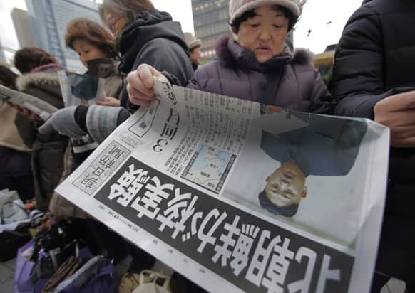 A woman reads a delivered extra edition of a Japanese newspaper reporting North Korea`s nuclear test, in Tokyo.