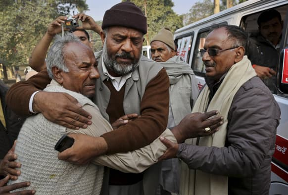 A man whose wife died in a stampede at a railway station, is comforted as he tries to arrange for the release of her body at a local morgue in Allahabad.