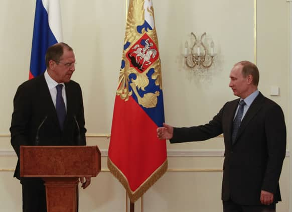 Russian President Vladimir Putin greets Foreign Minister Sergei Lavrov, left, during a meeting with Foreign Ministry officials at the Novo-Ogaryovo residence outside Moscow.