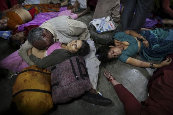 An Indian man weeps as he holds his wife who was killed in a stampede on a railway platform as other bodies are seen beside at the main railway station in Allahabad.