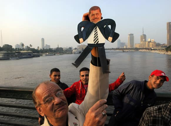 Egyptian artist Mohammed Darwish poses for a photograph with a puppet of Egyptian Islamist President Mohammed Morsi during an anti-Muslim Brotherhood protest on Qasr El-Nile Bridge, crossing the Nile river, in Cairo, Egypt.