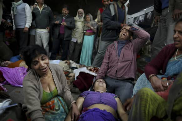 An Indian man weeps as he and other family members mourn next to the body of a relative who was killed in a stampede on a railway platform at the main railway station in Allahabad.