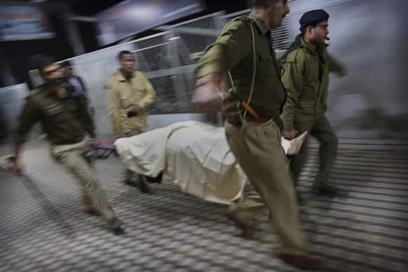 Indian police carry the body of a pilgrim who was killed in a stampede on a railway platform at the main railway station in Allahabad.