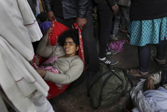 An injured Indian woman who survived a stampede on a railway platform is carried away at the main railway station in Allahabad.