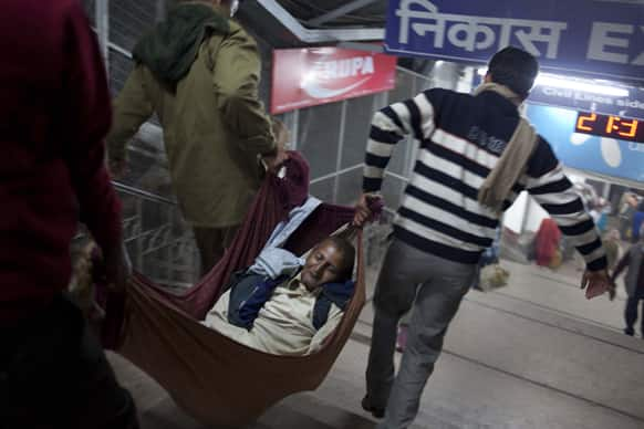 The body of a pilgrim is carried away after he was killed in a stampede on a railway platform at the main railway station in Allahabad.