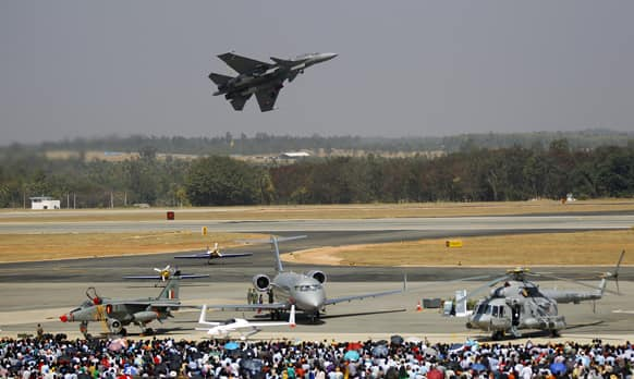 Visitors watch as Tejas, an Indian Air Force light combat aircraft flies over other aircraft on display, on the last day of the Aero India 2013 at Yelahanka air base in Bangalore.