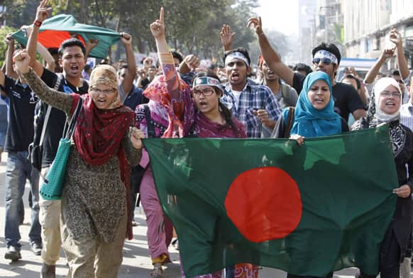Bangladeshi people shout slogans as they march carrying Bangladeshi flag demanding executions for people convicted of war crimes involving the nation`s independence war in 1971 in Dhaka, Bangladesh.