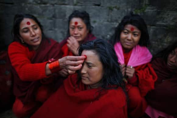 A Nepalese Hindu woman gets vermilion powder applied on her forehead after taking holy dips at the Bagmati River during Madhav Narayan festival in Katmandu, Nepal.