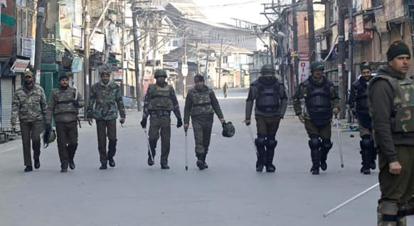 Policemen patrol a street on the second consecutive day of curfew imposed after the execution of a Kashmiri man convicted in a deadly 2001 attack on India`s Parliament in Srinagar.