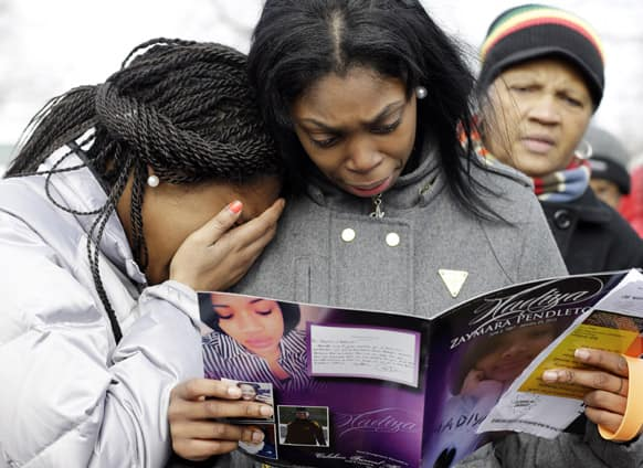 Danyia Bell, left, 16, and Artureana Terrell, 16, react as they read a program for the funeral of Hadiya Pendleton outside the Greater Harvest Missionary Baptist Church after the service, in Chicago.