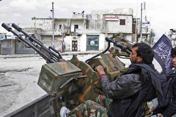 Free Syrian Army fighters sit behind their antiaircraft machine gun in Aleppo, Syria. Syrian rebels brought their fight within a mile of the heart of Damascus on Friday, seizing army checkpoints and cutting a key highway.