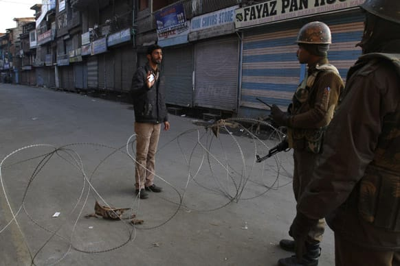 Paramilitary soldiers interrogate a civilian near a barbed wire set up as road blockade during curfew in Srinagar.