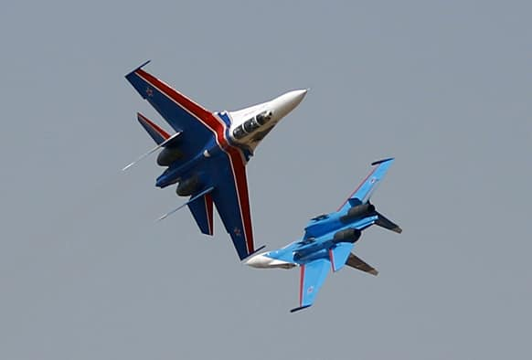 Russian air force aero demonstration team`s Sukhoi Su-27 fighters of the Russian Knights perform on the fourth day of the Aero India 2013 at Yelahanka air base in Bangalore.